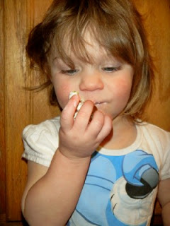 small child eating one of the potatoes