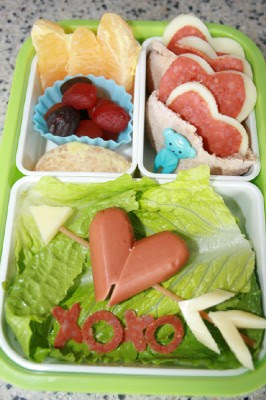 Valentines bento lunch box - hotdog heart, mini pitas sandwiches, fresh fruit and pepperoni cut into mini x's and o's