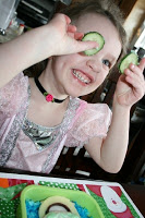 small girl holding up slices of cucumbers, smiling