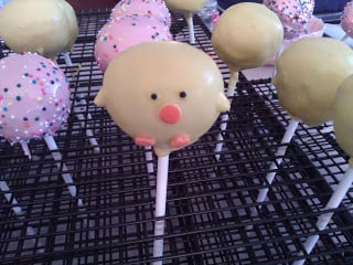 pink sprinkles and yellow chick cake pops drying on a wire rack