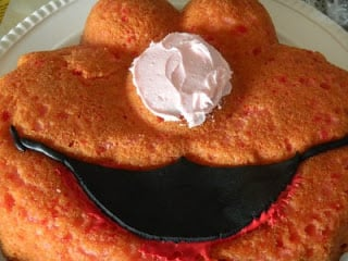 frosting on the nose of elmo cake and black fondant placed on his mouth