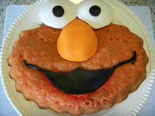 elmo cake with fondant eyes, nose and mouth placed on elmo cake
