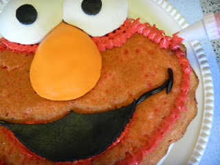 frosting the outer edges of elmo cake with piping bag and red frosting