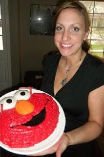 Woman in a black dress holding elmo cake