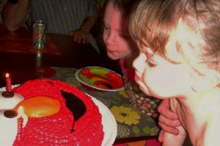 children blowing out candles on Elmo cake