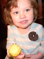 child holding a yellow cake pop
