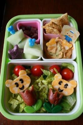 Top down picture of Bento Love : Tulips lunch box - hot dogs shaped like tulips, cheese shaped bears with nori eyes and mouth, fruit, humus and chips