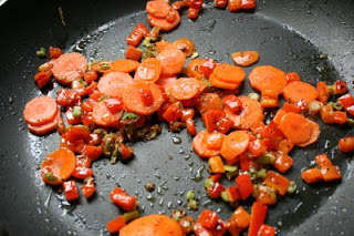 scallion whites, bell peppers and carrots cooking in a frying pan