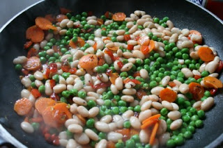 peas and white beans being added to vegetable mixture in frying pan
