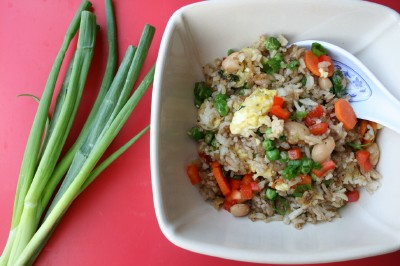 Top down photo fo the Fragrant Fried Rice Pilaf Recipe served in a off white bowl, with green onions on the side