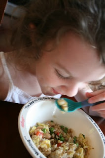 child sitting at a table eating the fried rice pilaf