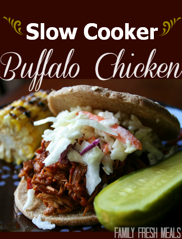 Side photo of the Slow Cooker Buffalo Chicken served on a bun and topped with cole slaw. On the side is a pickle and corn on the cob