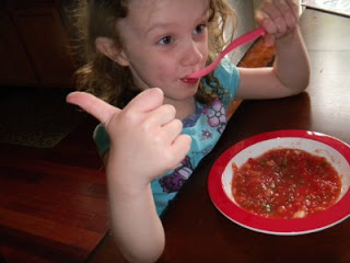 "child sitting at a table giving a ""thumbs up"" while eating the Tomato Watermelon Gazpacho"