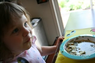child sitting at a table with bowl of soup in front of her