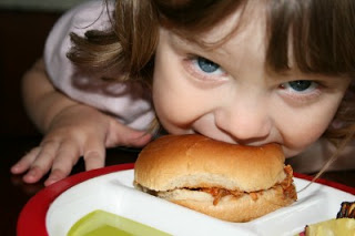 child biting into sandwich that is sitting on a plate
