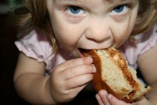 child biting into sandwich
