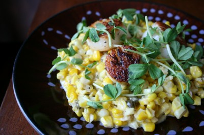 Creamed Corn and Scallops served on a dark plate and topped with peashoot