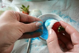 adding light blue sugar sprinkles to the lower part of strawberries