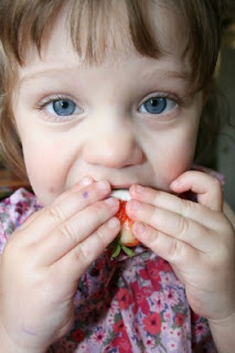 child eating a Red, White & Blue Chocolate Covered Strawberry