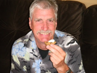 a man holding a Chocolate Chip Cookie Cups with Almond Buttercream Frosting, smiling.