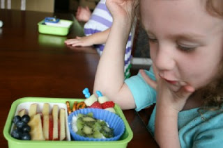 child sitting a a table looking at the Bento Love: Stars & Stripes 4th of July Lunchbox