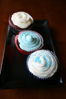 three frosted cupcakes sitting on a rectangle plate