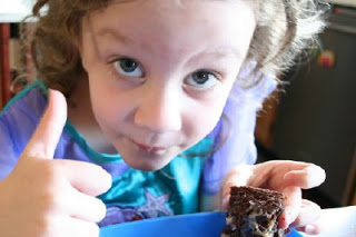 child giving a thumbs up while eating cake bar