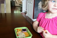 child sitting at the table with the cupcake surprise lunchbox