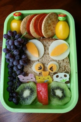 funny face sandwich packed in a lunchbox with fruit, cheese and crackers