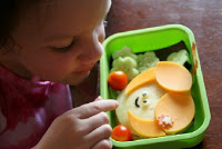 child sitting at a table looking at the lunchbox