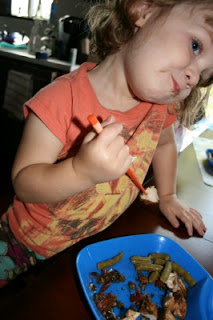 small child eating Thai Garlic & Basil Chicken with chopsticks