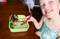 child sitting a table with back to school lunchbox, holding a piece of licorice