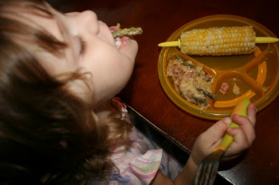child sitting at a table eating Cheesy Green Bean & Bacon Pot Pie