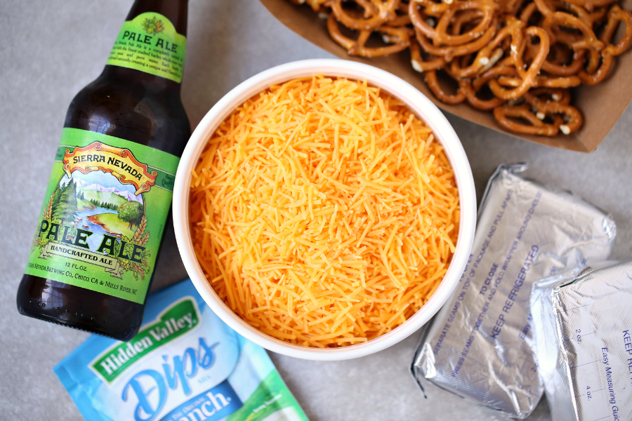 Beer Dip - Easy Party Dip Appetizer - Ingredients laid out. Shredded cheese, beer, cream cheese, pretzels and ranch dip