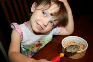 child sitting a table with a bowl of chicken salad appetizer