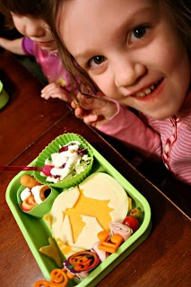 2 children sitting a table smiling with Witch Wonder Lunchbox