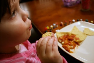child sitting at a table with a plate of pizza dip and tortilla chips