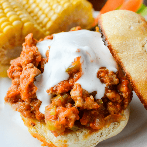 Buffalo Sloppy Joes served on a toasted bun, with corn on the cob on a white plate