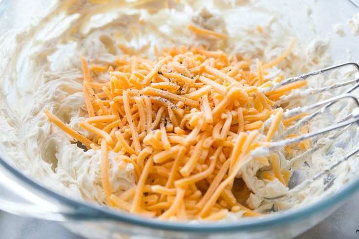 Mini Cheese Balls - Cream cheese seasoning and shredded cheese mixed in a glass bowl