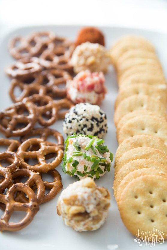 Mini Cheese Balls Recipe served on a white plate with crackers and pretzels via @familyfresh