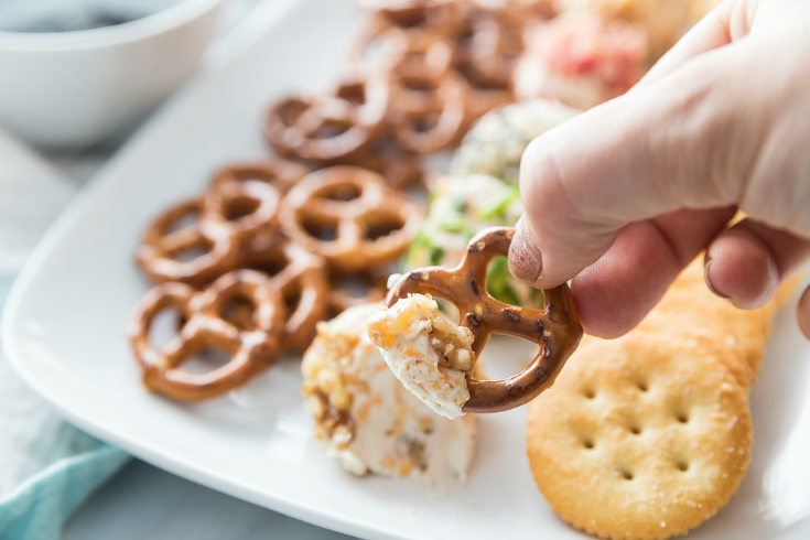 Mini Cheese Balls - scooping mini cheese ball with a pretzels