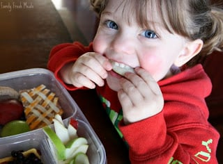 Child sitting at a table eating the A Tisket, A Tasket lunchbox
