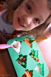 child sitting at a table with Muffin Tin Meal Olive My Christmas Tree