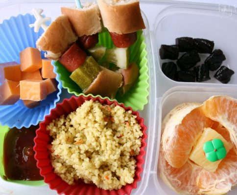 Top down picture of Hot Dog Kabob lunch box - hot dog kabobs, couscous, cheese cubes, orange slices and fruit snacks