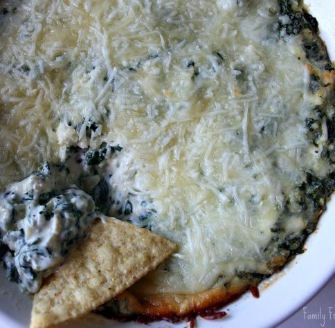 Spinach Artichoke Dip in a baking dish, with a tortilla chip scooping out some dip