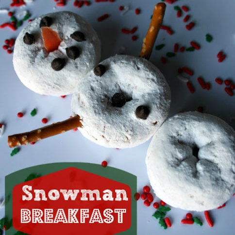 Snowman made of powdered mini donuts, pretzels and mini chocolate chips, on a white plate, surrounded by holiday food sprinkles