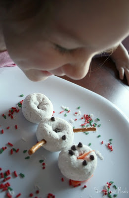 child sitting at a table, looking and smiling at donut snowman