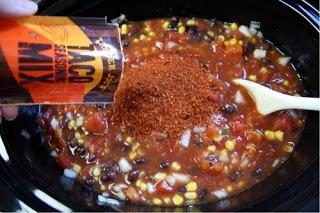 Crockpot Chicken Taco Soup  - Sprinkling taco seasoning into crockpot