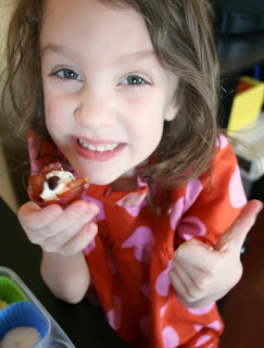 Small child eating a Prosciutto Cups with Cheese & Herb Filling and giving a thumbs up