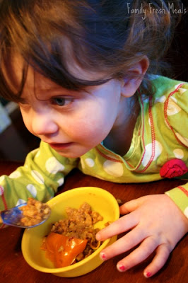 small child eating a stuffed pepper at a table